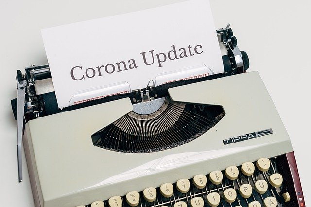 typewriter with paper that has corona update written on it